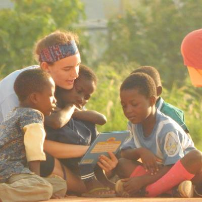 A Projects Abroad volunteer reading to children at her Spring Break Childcare Project in Ghana